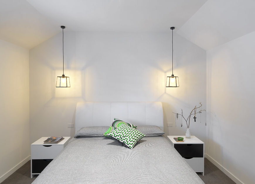 The primary bedroom stands in the same minimalist style as the open plan living and dining room area. White walls stand over grey carpet and a grey toned bed, flanked by a pair of white bedside tables and metal frame pendant lights.
