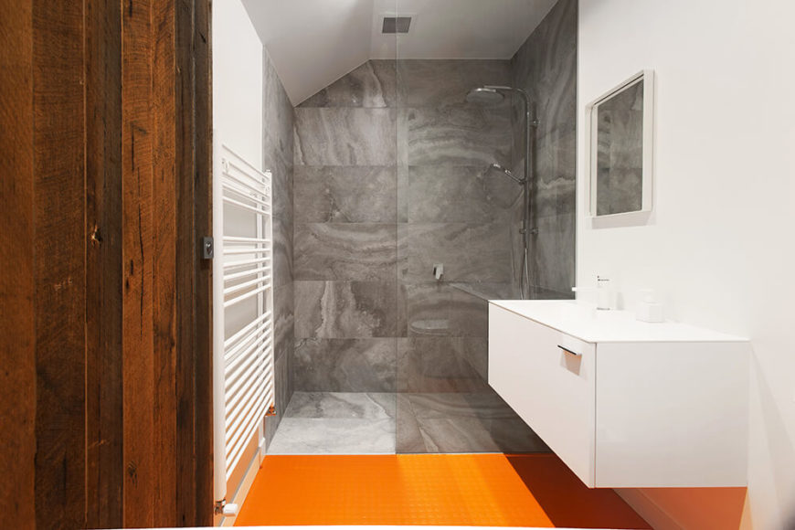 The primary bathroom sports a bold orange floor in high contrast with the rest of the home's muted palette. This is complemented by a floating white vanity and walk-in shower wrapped in marble.