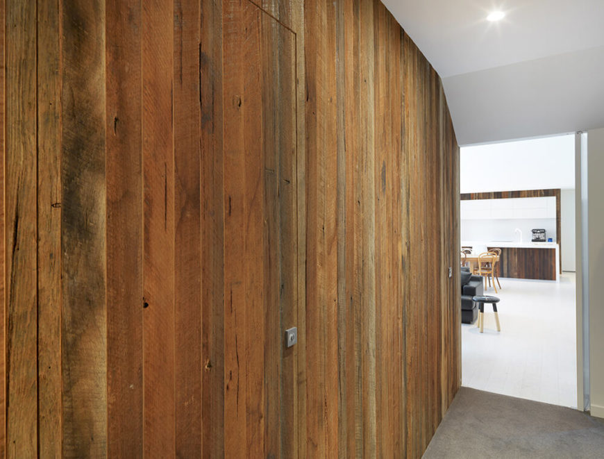 The rich wood paneling extends down a hall, making a clear distinction from the all-white open plan parts of the home. This wall obscures a pair of hidden doors, marked only by square handles.