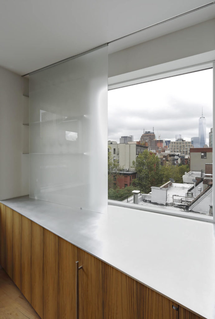 The kitchen area has plenty of storage space and large windows that look out over the city skyline. The mixture of wood and inorganic materials keeps the modern design from feeling too stark and sterile.