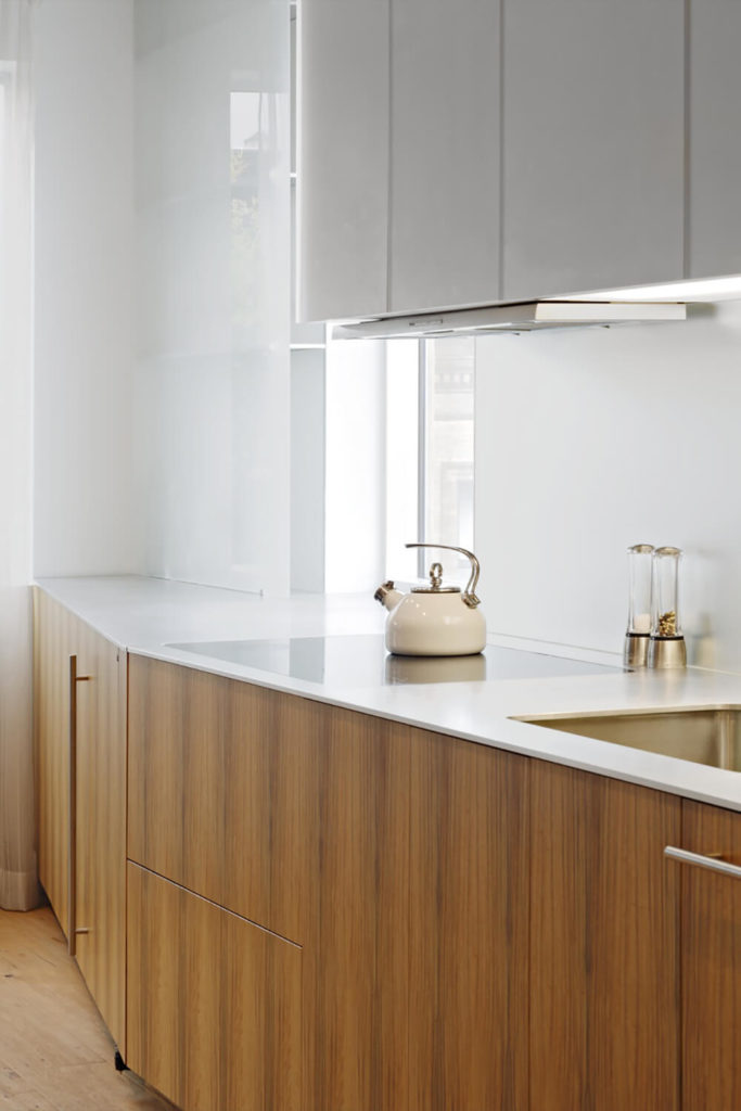 The warm color and rich texture of the wooden cabinetry keeps the room from feeling too light, or the contrast from feeling too stark. The stove consists of a ceramic cooktop that is built into the countertops.