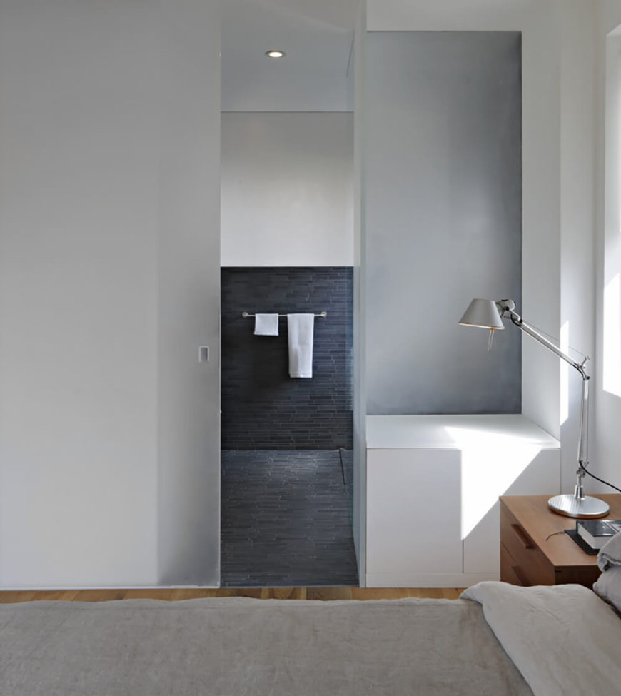 The primary bedroom has an en suite bathroom in layered charcoal colored tiles, which create a soothing, yet contrasting environment.