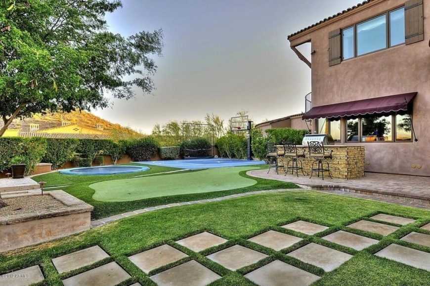 This fully loaded backyard has a number of amazing activities. You can go into this backyard for a bit of golf, a game of basketball, or to jump on the trampoline. The trampoline adds that extra level of recreation, putting this backyard over the top as a fun space.