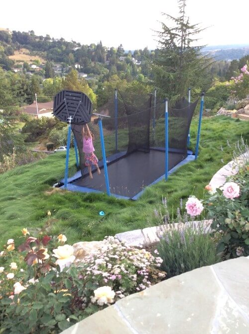 This buried trampoline has a safety net and a basketball hoop. Not only will your kids be safer in this kind of setup but they will also be able to make amazing funky dunks.
