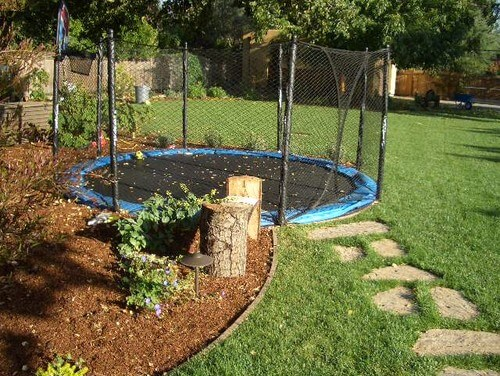 Here is a trampoline that is buried as well as equipped with a safety net fence. If someone falls they will be caught by the net. If for some reason the net is not enough to catch them, their fall will not be as far as it would have been if the trampoline were not buried.