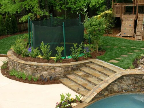 Rather than burying the trampoline in the ground, the ground was built up around this trampoline. This provides the same safety benefits as burying it but also lets you play with landscaping and gardenwork.