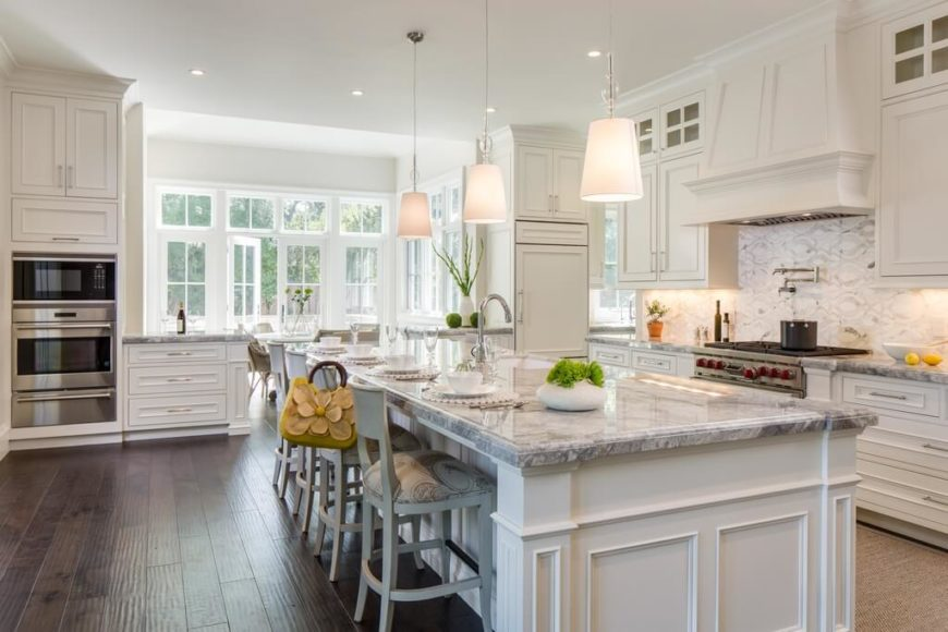 White kitchen with plenty of windows and a spacious island.