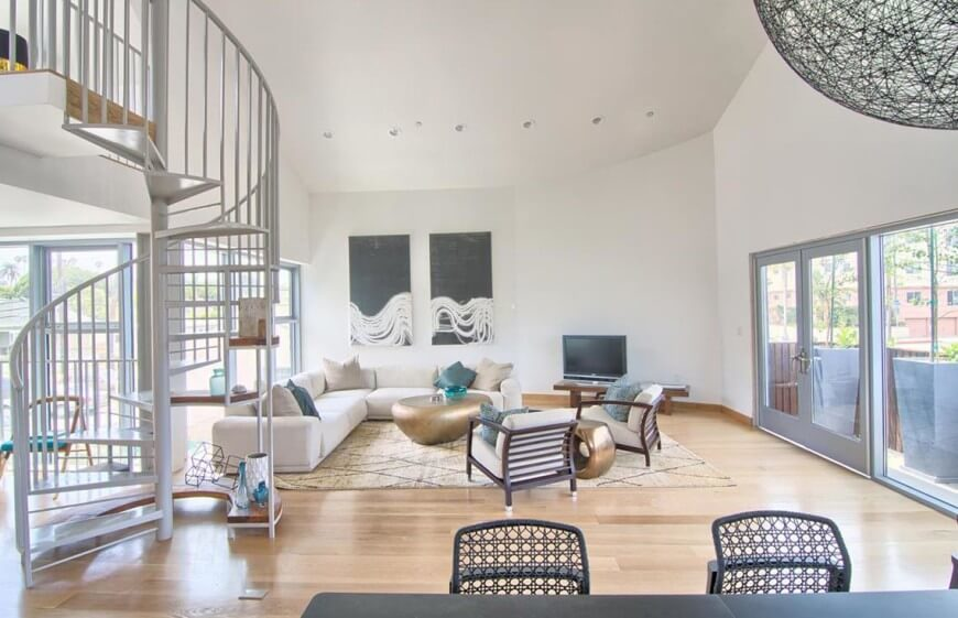 Airy living room with a nearby spiral staircase.