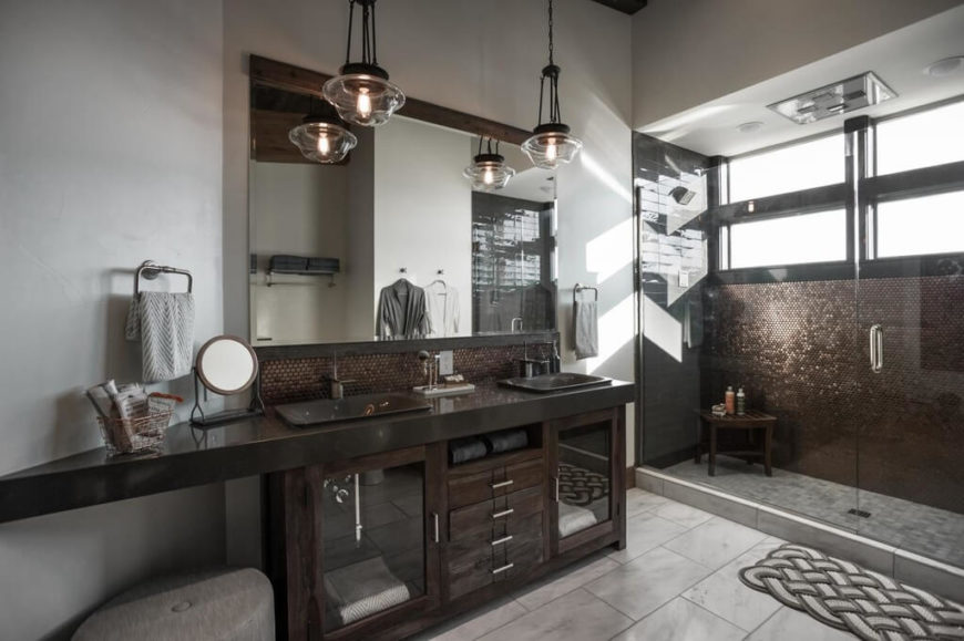 Dark bathroom with rich wooden vanity and glittering tile.