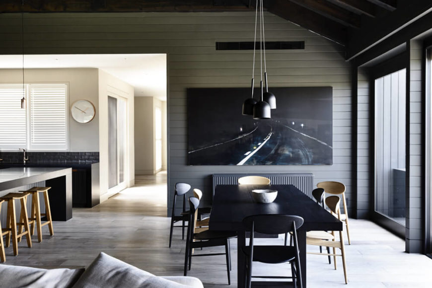The dining area centers on a large black wood table and assortment of natural wood chairs. From here, we can see the main hall leading to the bedrooms, drenched in sunlight.