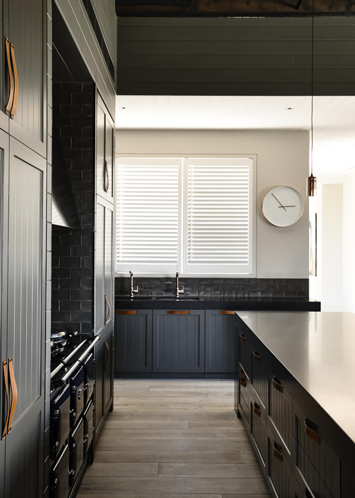 Moving inside the kitchen, we can glimpse the elegant dark toned cabinetry with unique leather strap handles, adding a touch of old school farmhouse charm. The countertops and oven appear in black as well, keeping the tone neat.