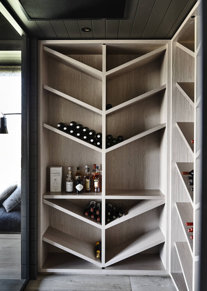 Tucked away is this unique angular wine cellar, a simple but bright corner of the home design that allows for bottles to be stored in an elegant and fashionable way.