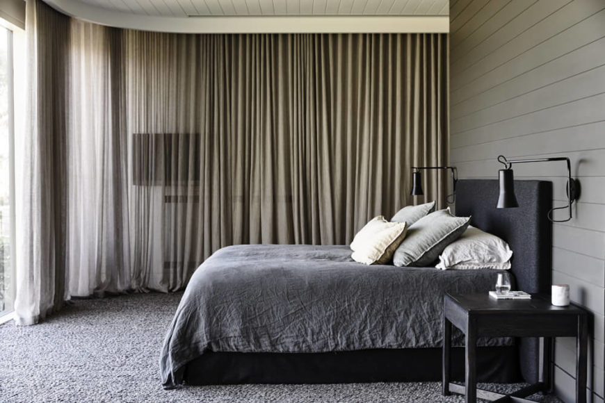 The primary bedroom also features massive floor to ceiling windows, which necessitated the inclusion of wraparound curtains for privacy and darkness. The muted color scheme appears here unbroken.