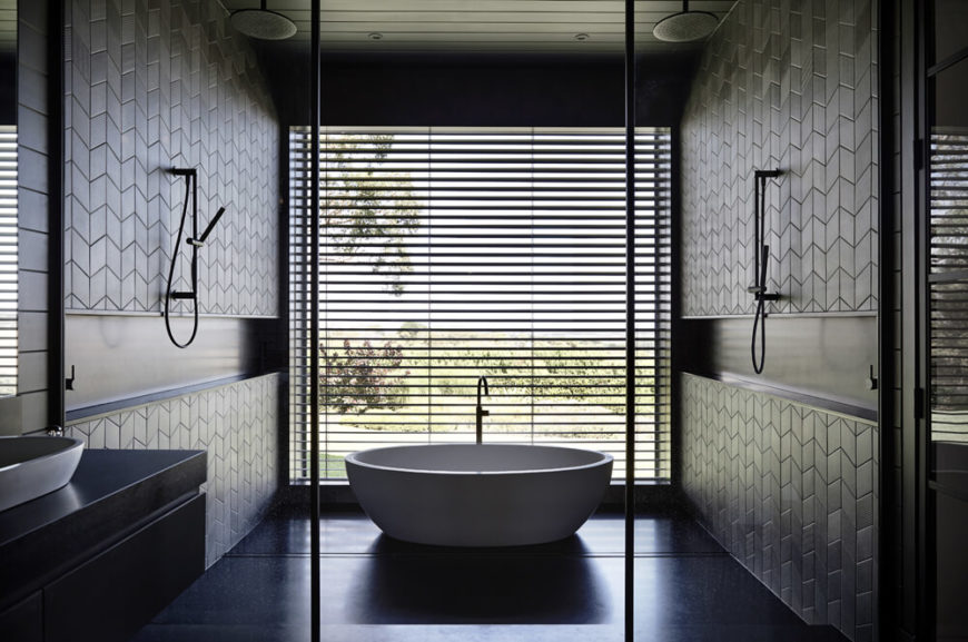 The primary bathroom centers on this huge bathing area, a small room within a room containing shower function and a bold white pedestal tub. The huge window provides exquisite views from the bath while shades keep privacy.