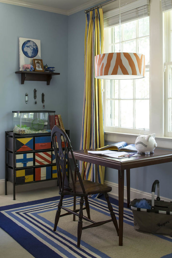 The bedroom features loads of particular details, including this rich wood writing desk and the international flag dresser seen at left. It's a riot of color within the more reserved home.