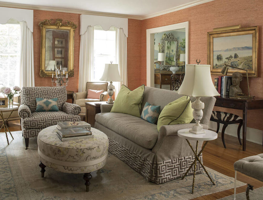 The living room is wrapped in warm salmon tones, with a textural wallpaper finish that helps connect the various artworks and other important details throughout the room. Furniture selection leans toward traditional shapes with modern tones.
