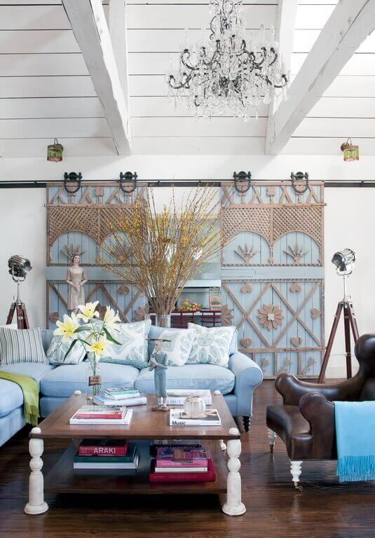 In a remarkable departure from the typical style associated with sliding barn doors, this home's are in a beautiful light blue and embellished with light wood shapes and patterns.