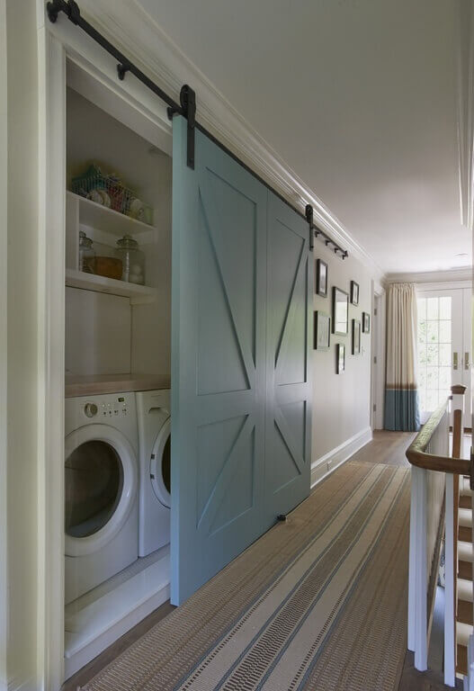 The laundry room has been hidden behind this large sliding barn door in light blue. The door is a perfect way to take advantage of closet space in a narrow hallway, where a door may be difficult to open and close.