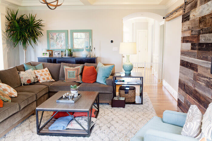 In a contemporary room, utilizing different colors and textures of wood in the door creates texture and visual interest. This cozy living room already features a wealth of colors and patterns.
