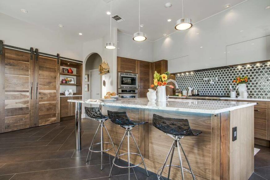 The sliding barn doors in this kitchen can be slid away to reveal open shelving and pantry space. The usage is a unique way to deal with open shelving and the clutter it can sometimes create.