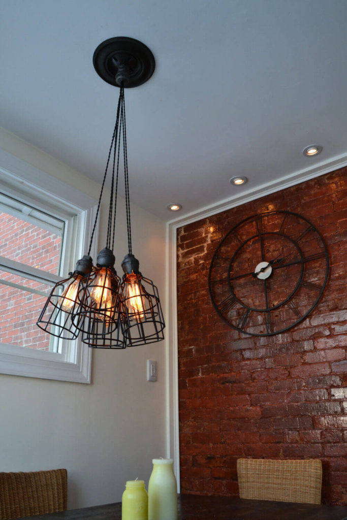 A flexible industrial light that will look great in nearly any room in your home. The wires used to hang the lights are cloth-covered, as vintage lights would have been. The cages on each of the lights may be removed if desired. The lights are pre-wired. A clip may be used to adjust each cord to the desired length.