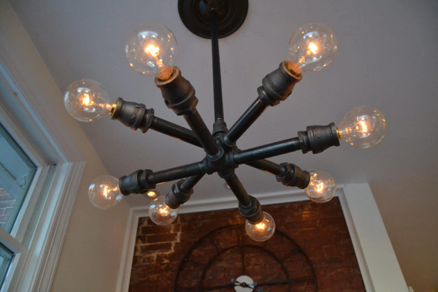 This unique light fixture has two layers of lights that form a star-like shape. Each of the lights is fitted with an Edison bulb. The light comes with a 12 inch pole to connect to the ceiling, but can be customized with a longer or shorter pole.