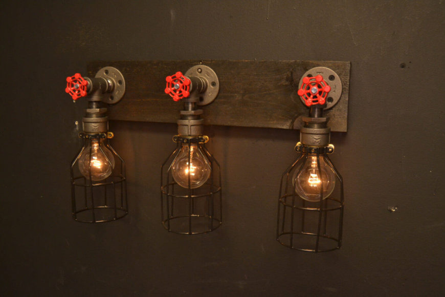 This series of three lights is perfect for a bathroom vanity, featuring matching faucets, Edison bulbs, and black metal cages around the bulbs.