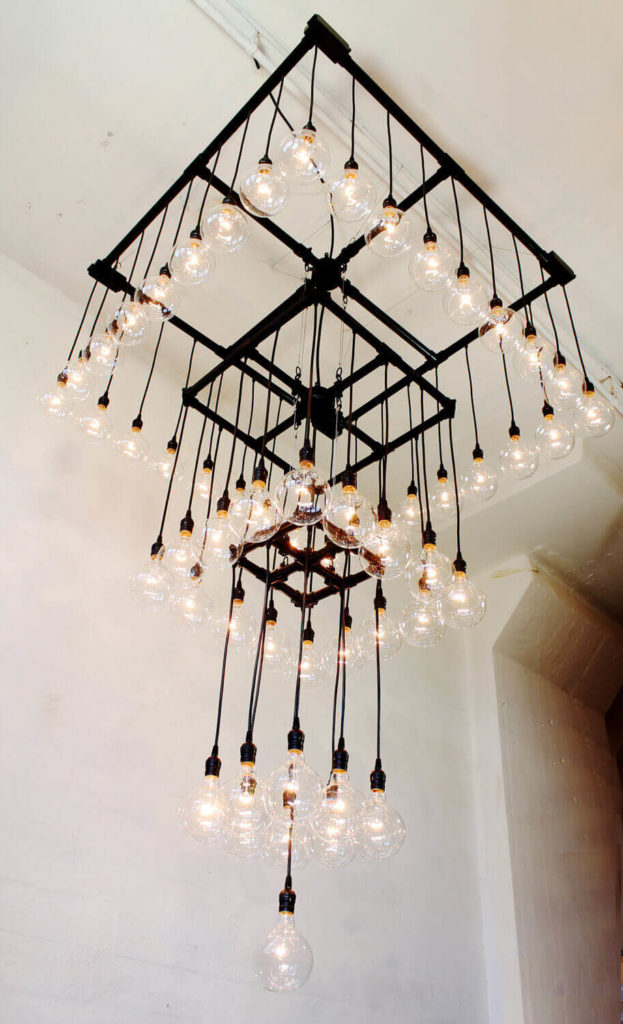 This massive industrial chandelier has four tiers, so it's suitable for a large space with massively tall ceilings. The fixture weighs about 30 pounds, and includes 57 bulbs, each one at 25 watts. For smaller spaces, the light can be scaled down to match, keeping the proportions of the original structure.
