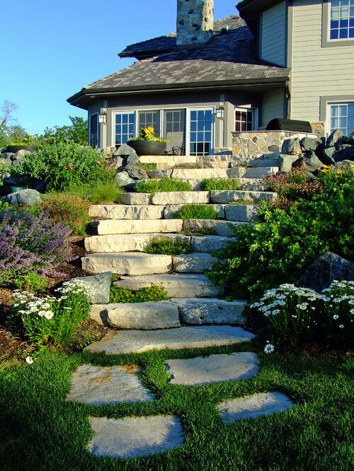 Stones come in many different colors and styles. These stone steps are light and bright. These stones pair very well with the vibrant greens and whites of the grass and flowers.