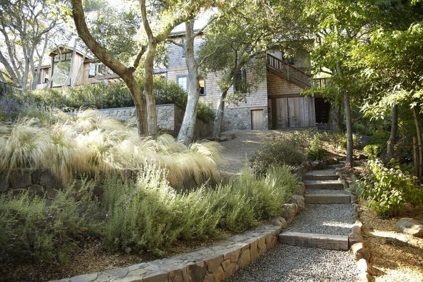 Here is a layered yard with some unconventional use of grass. The tall and flowing grasses on the top layer are allowed to spill over the brick, giving this yard an interesting shaggy and natural look.