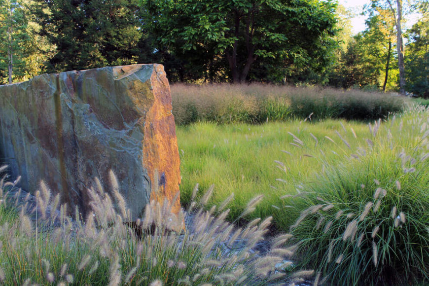 If you don't have association rules to follow, you may decide to let your grass grow out. This yard has a large patch of grass that has grown out substantially. This wild and shaggy aesthetic is a great stage for naturally cut rock features.