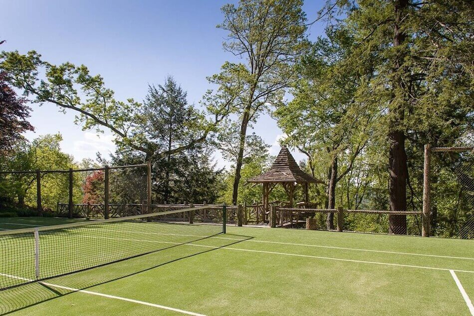 Backyard tennis court surrounded by chain link fence