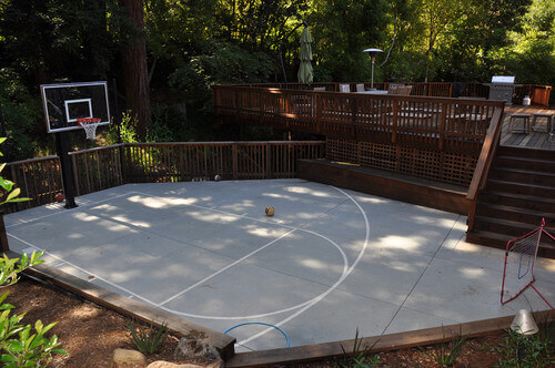 Here is a simple painted half court that sits right off of this deck. This is an amazing space to go out and practice basketball skills. Because of the simplicity of this space and the concrete build, this court can be used for multiple purposes other than basketball.