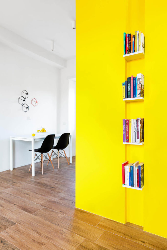 Along the bright yellow wall in the open plan space we see a series of small bookshelves, creating both a utilitarian and artistic flourish that adds a second layer of color and detail to the bright space.