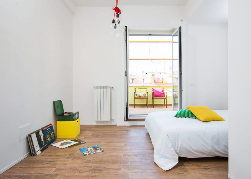 Here we have the primary bedroom, a white minimalist space with plenty of room for activities. The owner's record collection sits along with a bold yellow box to the left, while we can see the terrace through double doors.