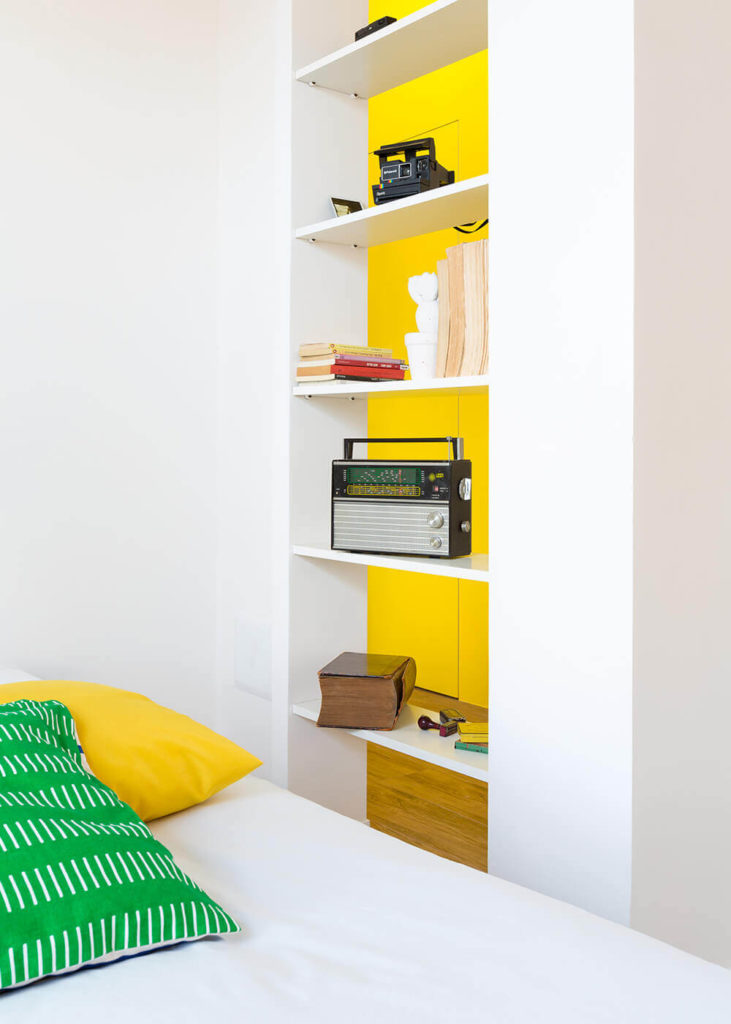 The bedroom features more integrated bookshelves, this time an open design that allows for a visual pass through between the bedroom and rest of the home.