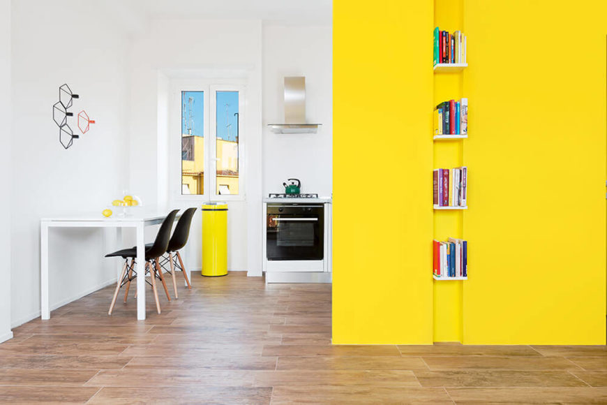 Returning to the wider space of the main open plan living room area, we see how it connects to the white, minimalist kitchen and how the bold yellow color reappears throughout the home.