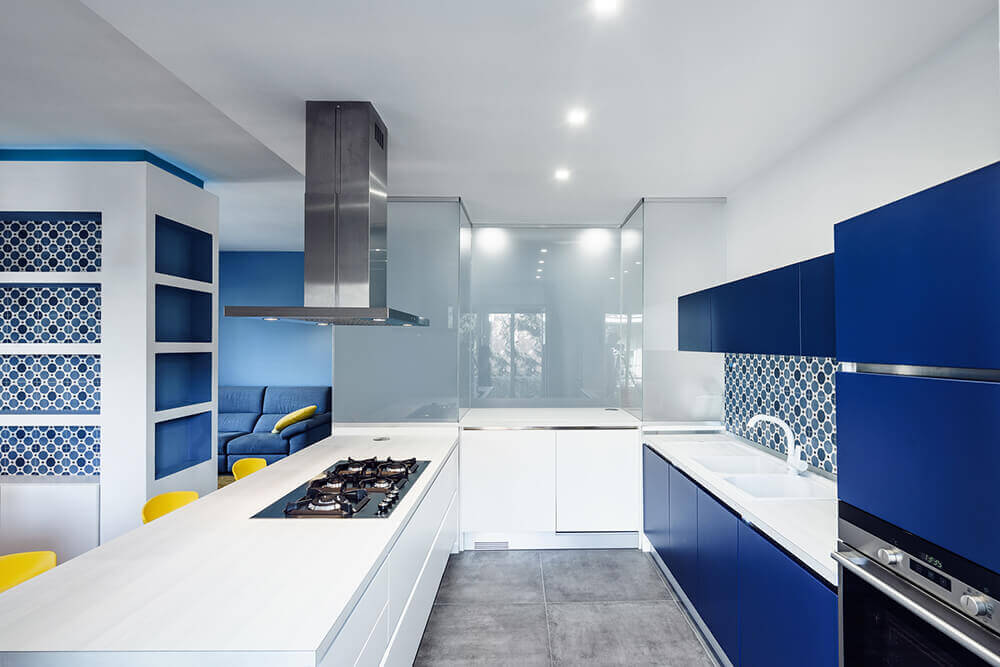 Stunning white kitchen with blue shade. The smooth countertops are just perfect together with the recessed ceiling lights.