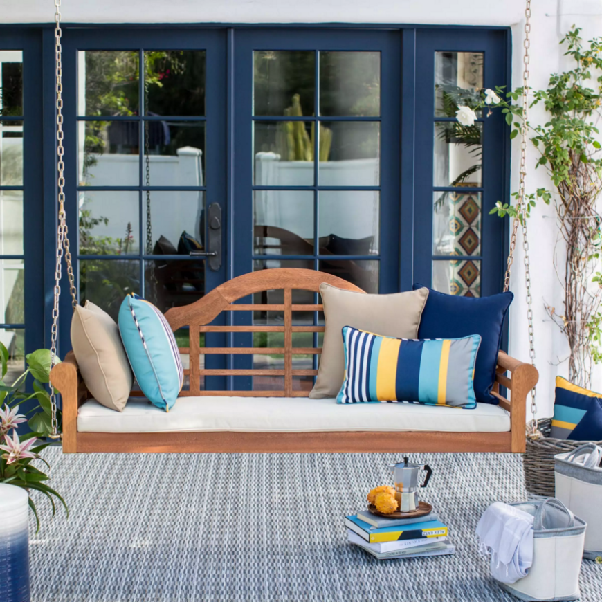 Suspended above this porch is a lovely crafted wooden porch swing with a padded seat. This kind of swing is suspended with chains, so make sure to install it properly on a structure that can handle the strain of a suspended swing.