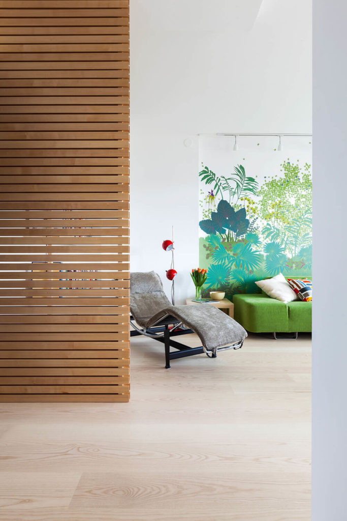 A simple perforated dividing wall, made of rich natural birch, helps define the living room area within the larger open plan layout.