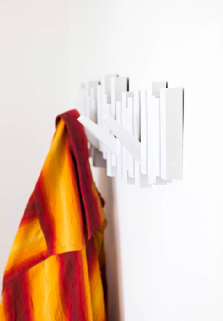 Small details abound throughout the apartment, including this sleek white coat hanger on the wall. Almost invisible until it's needed, the piece reflects the artistic approach of the design.