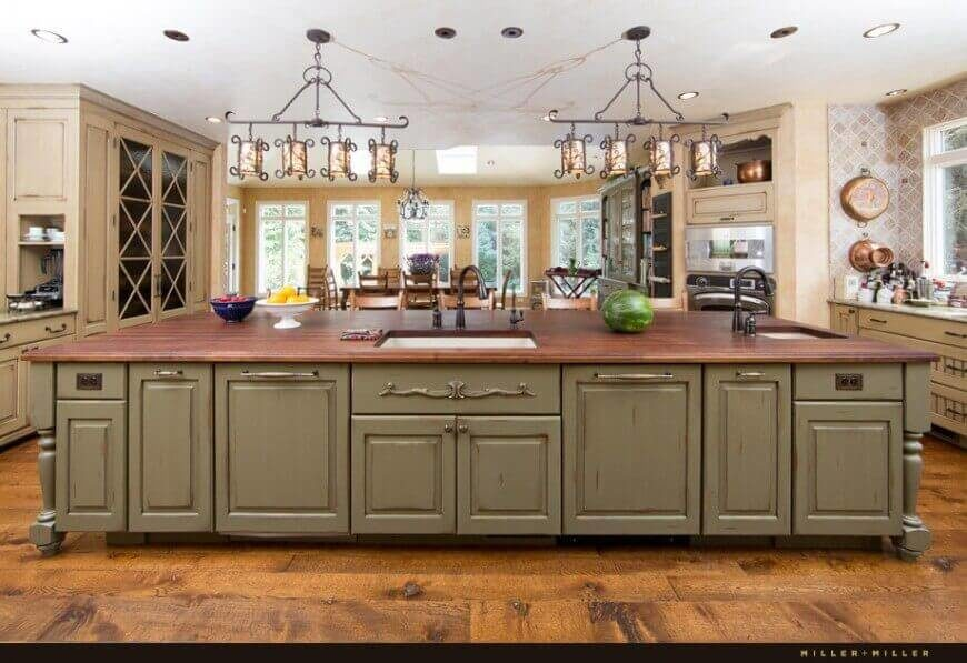 This open and spacious Mediterranean kitchen has a very large island to increase counter space and storage.