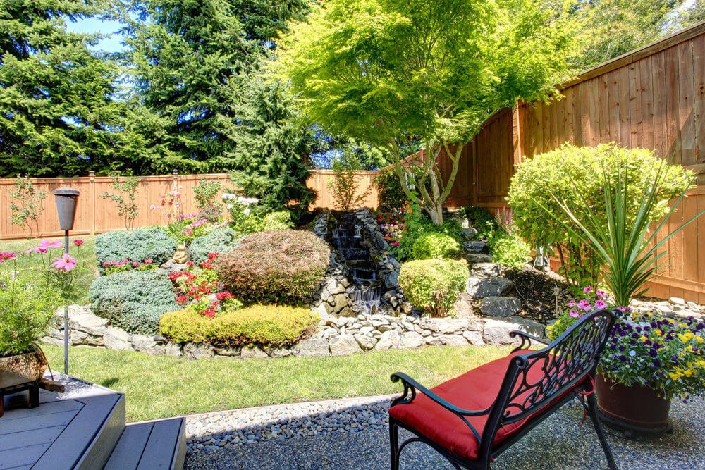 Stunning small garden with rock border and small waterfall.