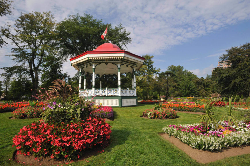 This stylish and bright gazebo sits in the center of a lovely yard surrounded by patches of gardens. When purchasing a permanent hardtop gazebo you can paint it to match your garden colors.