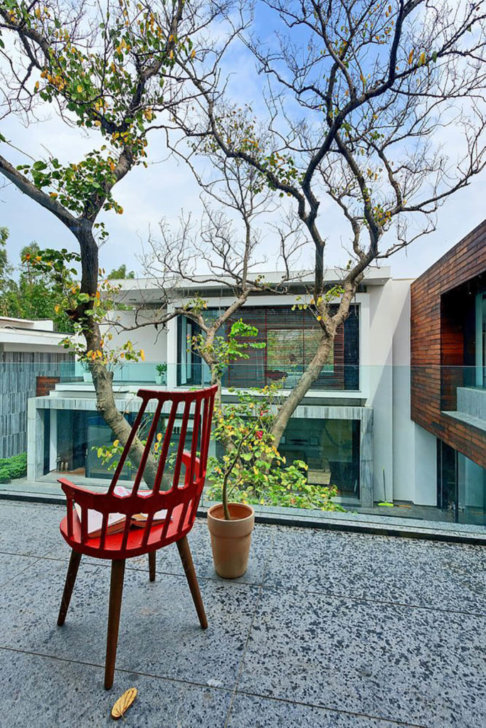 On a second floor balcony, we see a great view of the courtyard and surrounding pieces of the home, wrapped in brick, marble, and rich wood tones. The tree commands attention at the center.
