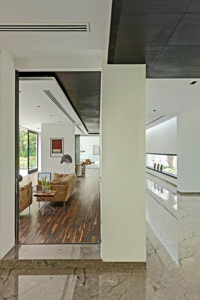 Further along in the home, we see lengthy rooms filled with rich hardwood flooring, marble, and expanses of pristine white walls. The furniture is a mixture of neat, midcentury modern designs.