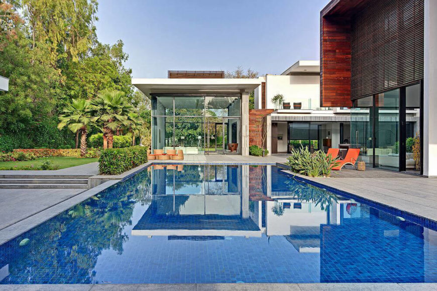 Moving around the side of the structure, we see the large swimming pool reflecting the home across the courtyard. This intricately crafted space mixes sharp modern design and an invitation to nature.