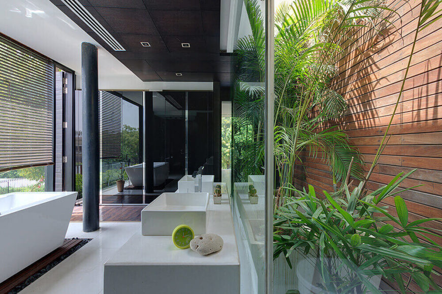 The mater bath is a striking modern space, mixing glass, white marble, rich natural wood, and rows of bright greenery. A pedestal tub at left can be enjoyed with wraparound views of nature.