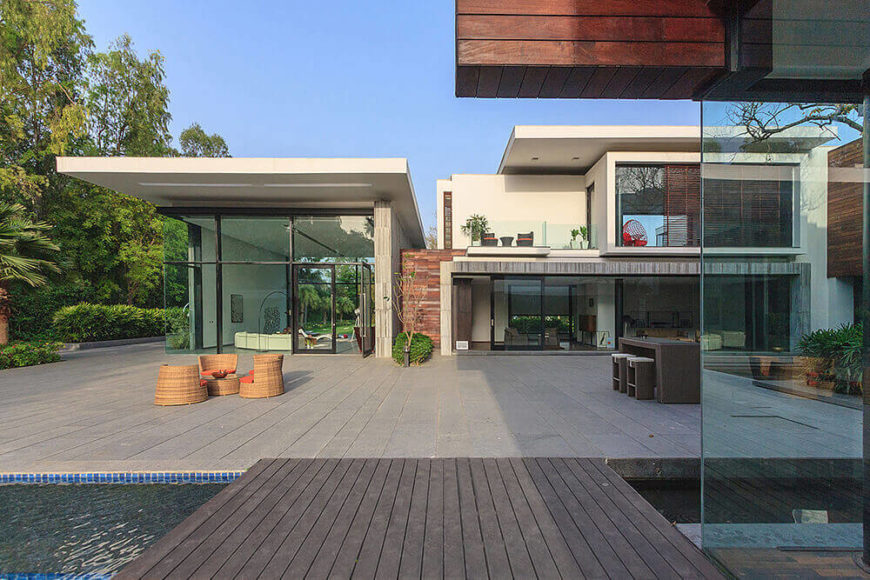 Across the vast courtyard, we see a large sunning room, living room, bedrooms up top, and an abundance of full height glass and sliding doors. The focus of the entire home is a direct interaction with nature.