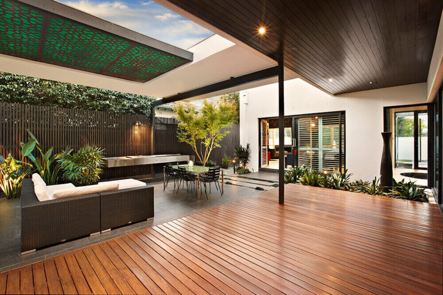The expansive timber deck works as a bridge between the home itself and the granite flooring of the dining area. Above, an extended overhang provides protection from the elements.